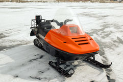 Orange snowmobile on ice. Orange snowmobile on the ice of Lake Baikal Royalty Free Stock Photos