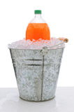 Orange Soda Bottle in Bucket of Ice. An orange two liter soda bottle in a metal bucket full of ice on a wet countertop. Vertical format over a white background Royalty Free Stock Image