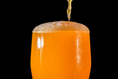 Orange soda large glass, overflowing glass of orange soda closeup with bubbles isolated on black Royalty Free Stock Photo