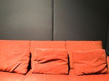 Orange sofa and black wall Stock Photos