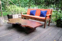 Orange sofa Color and wooden table in garden. royalty free stock photos