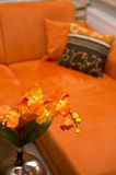 Orange sofa with flower. Orange sofa or couch detail with flower in focus Stock Photo