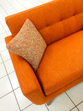Orange sofa with decorative cushion Stock Image