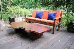 Orange Sofafarbe und -Holztisch im Garten lizenzfreie stockfotos