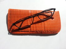Orange soft eyeglass case with glasses against white background Royalty Free Stock Photography