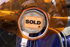 Orange sold sticker on scooter headlight in shop, close-up, front view Royalty Free Stock Image