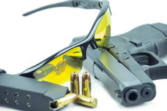 Orange solexponeringsglas och 9mm svart vapenpistol som isoleras på vit bakgrund Arkivbilder