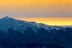Orange solnedgång över berg Arkivbild