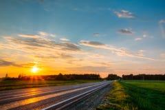 Orange solnedgång över skogen och huvudvägen inget Arkivfoton