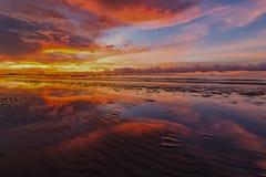 Orange solnedgång med brinnande himmel och den reflexion Arkivbild