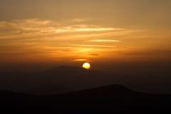 Orange solnedgång med moln i berg royaltyfri bild