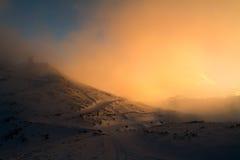 Orange solnedgång med moln i berg arkivbilder
