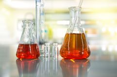 Orange solution in flask cylinder vial in science laboratory bac. Orange solution in flask cylinder vial in chemical science laboratory background Stock Photos