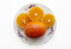 Orange. An orange and some of pieces in a plate Royalty Free Stock Images