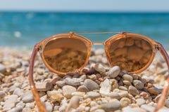 Orange Sonnenbrille auf dem Strand Stockfotografie
