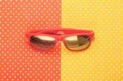 Orange Sonnenbrille mit buntem erstklassigem Hintergrund stock abbildung