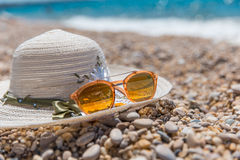 Orange Sonnenbrille und weißer Hut auf dem Meer setzen auf den Strand Stockbild