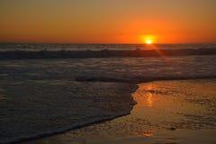 Orange Sonnenuntergang über den Wellen an Santa Monica Strand stockbilder