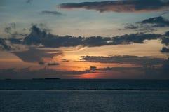 Orange Sonnenuntergang auf dem Indischen Ozean: rosa und orange Blitze von der untergehenden Sonne, lange graue Kumuluswolken auf Lizenzfreie Stockfotos