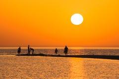Orange Sonnenuntergang auf dem Strand Stockfotografie