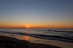 Orange Sonnenuntergang auf dem Strand somethere nahe Tallinn, Estland Lizenzfreie Stockfotografie