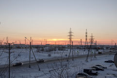 Orange Sonnenuntergang auf der industriellen Straße des Winters Ansicht vom Fenster am eisigen Abend Lizenzfreie Stockfotos