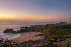 Orange Sonnenuntergang auf einer Landschaft mit Strand und Kirche lizenzfreies stockfoto