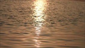 Orange Sonnenuntergang an der See- und Sonnenlichtreflexion auf dem Wasser stock footage