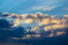 Orange Sonnenuntergang, wo die Sonne von unterhalb der Wolken heraus spähen ausstrahlt, Stockbilder