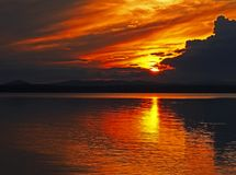 Orange Sonnenunterganghimmel und Sonne über dem See, goldene Stunde stockbild