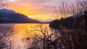Orange Sonnenuntergangreflexionen auf einem See mit Bergen und einem bewölkten Himmel Lizenzfreies Stockfoto