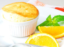 Orange Souffle. Dish with orange souffle on plate, decorated with orange slices, chopped nuts and mint leaves Royalty Free Stock Photography
