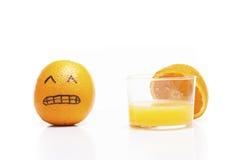 Orange soumise à une contrainte près d'un verre de jus ! Image libre de droits