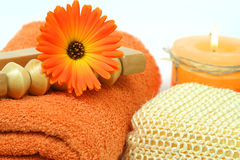Orange spa tools. Spa tools in orange color - towel, marigold flower and burning candle stock photography