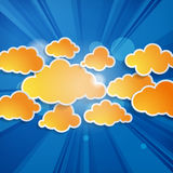 Orange speech bubbles in the shape of clouds with rays. Abstract orange speech bubbles in the shape of clouds with rays on a blue background Royalty Free Stock Photography
