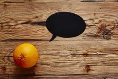 Orange with speechbubble on wooden board.jpg. Orange with speechbubble on wooden board Stock Photography