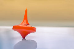 Orange spinning top Stock Photos