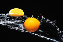 Orange with splash on a black Stock Photos