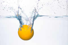 Orange splash in water Royalty Free Stock Photos