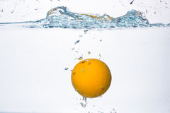 Orange splash in water Royalty Free Stock Photo