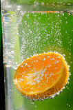 Orange splashing into clear water Stock Image