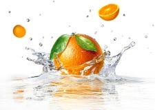 Orange splashing into clear water Royalty Free Stock Images