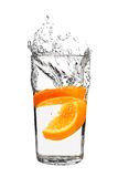 Orange splashing into glass of water Stock Photography