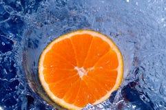 Orange splashing water Royalty Free Stock Photo