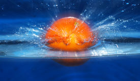 Orange splashing in water blue background Stock Photos