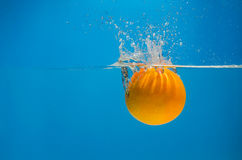 Orange splashing in water with blue background Stock Photos