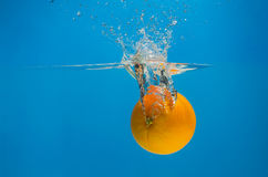 Orange splashing in water with blue background Stock Image