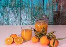 Orange split in half with a glass and a jug of orange juice royalty free stock images