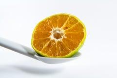 Orange with spoon Stock Photos