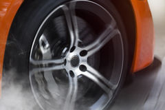Orange Sport Car with detail on spinning and smoking wheels/tires doing burnouts Royalty Free Stock Photography